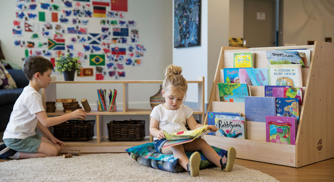 Two children learning in a small library curated for children
