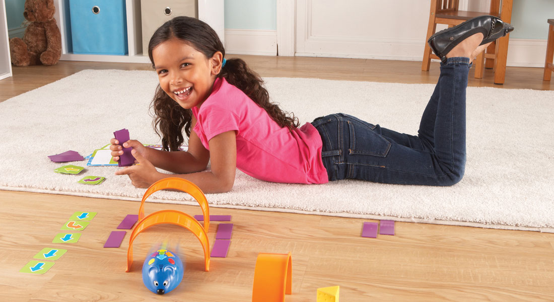 Young girl playing with science toys on rug