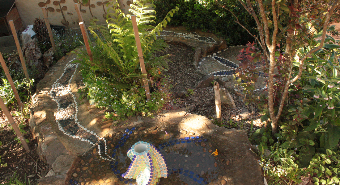 Garden with art made by children covering the rocks
