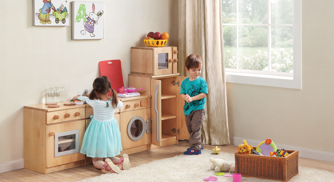 Children experiencing pretend play in a mock up kitchen