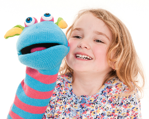 Young girl playing with a blue and pink puppet