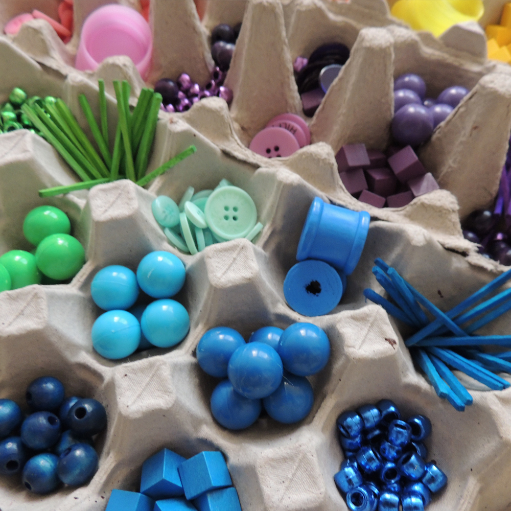 A selection of colourful beads and other loose parts stored in egg cartons