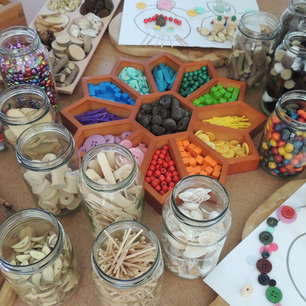 Well organised image of loose parts stored in a sorting tray and glass jars