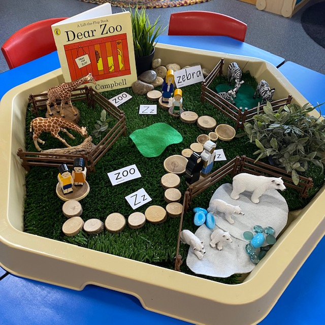 Dear Zoo Hex Tray activity featuring book animals and wooden blocks on grass