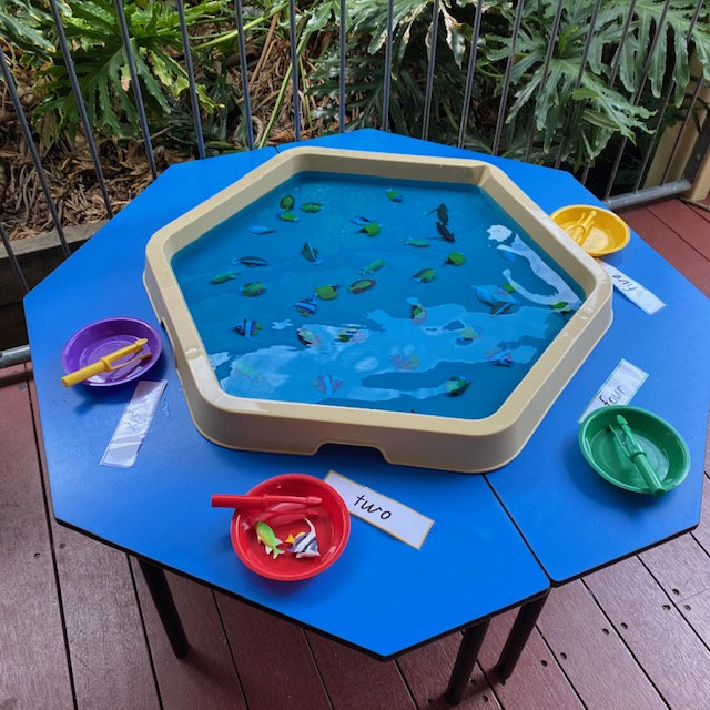 Number fishing Hex Tray activity featuring plastic numbered fish in water