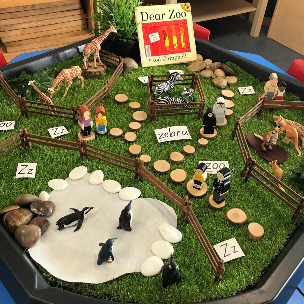Dear Zoo Active World Tray activity featuring book animals and wooden blocks on grass