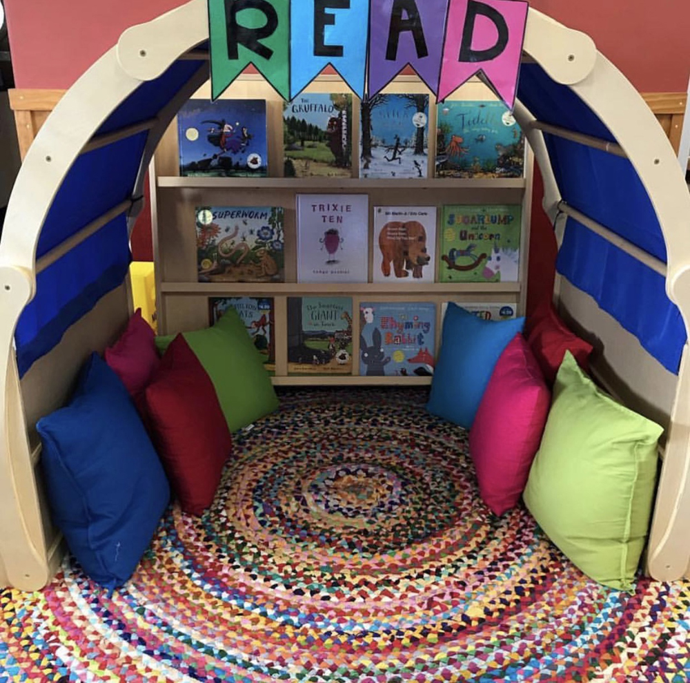 Cosy reading corner with a rug, cushions, and book shelf