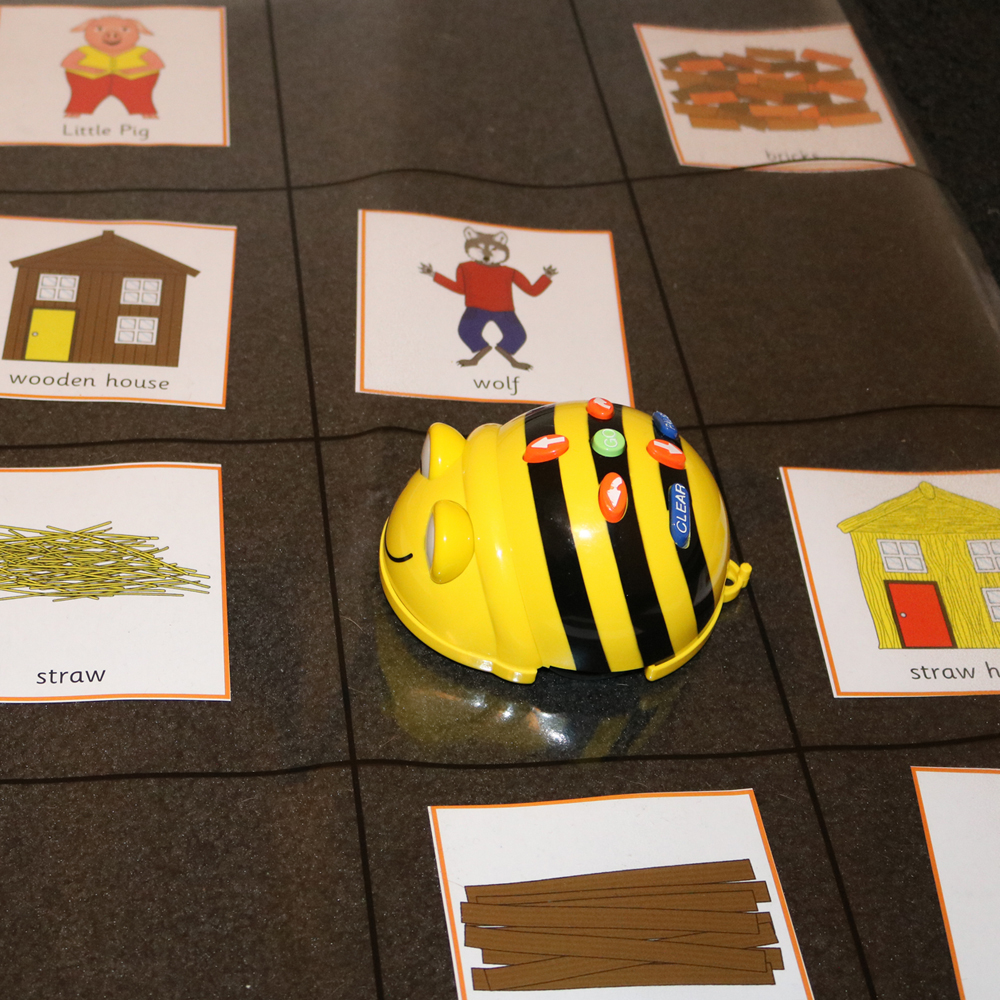 Retelling stories with Beebot and three little pig images on map