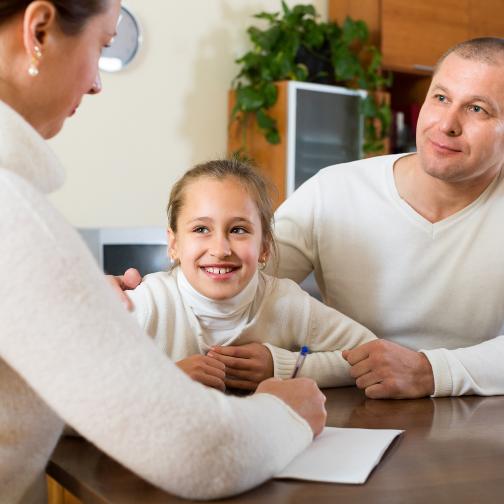 Young girl sitting at a table with parents