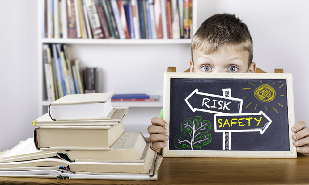young boy holding up a black board with the sign risk and safety