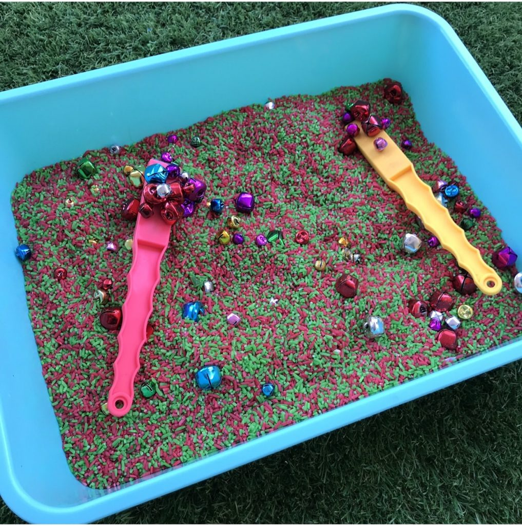 Sorting christmas bells in coloured rice with magnet wands