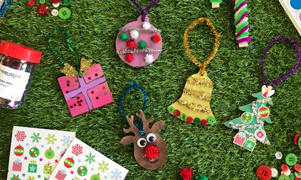 Christmas decorations spread featuring ornements and christmas stickers on grass background