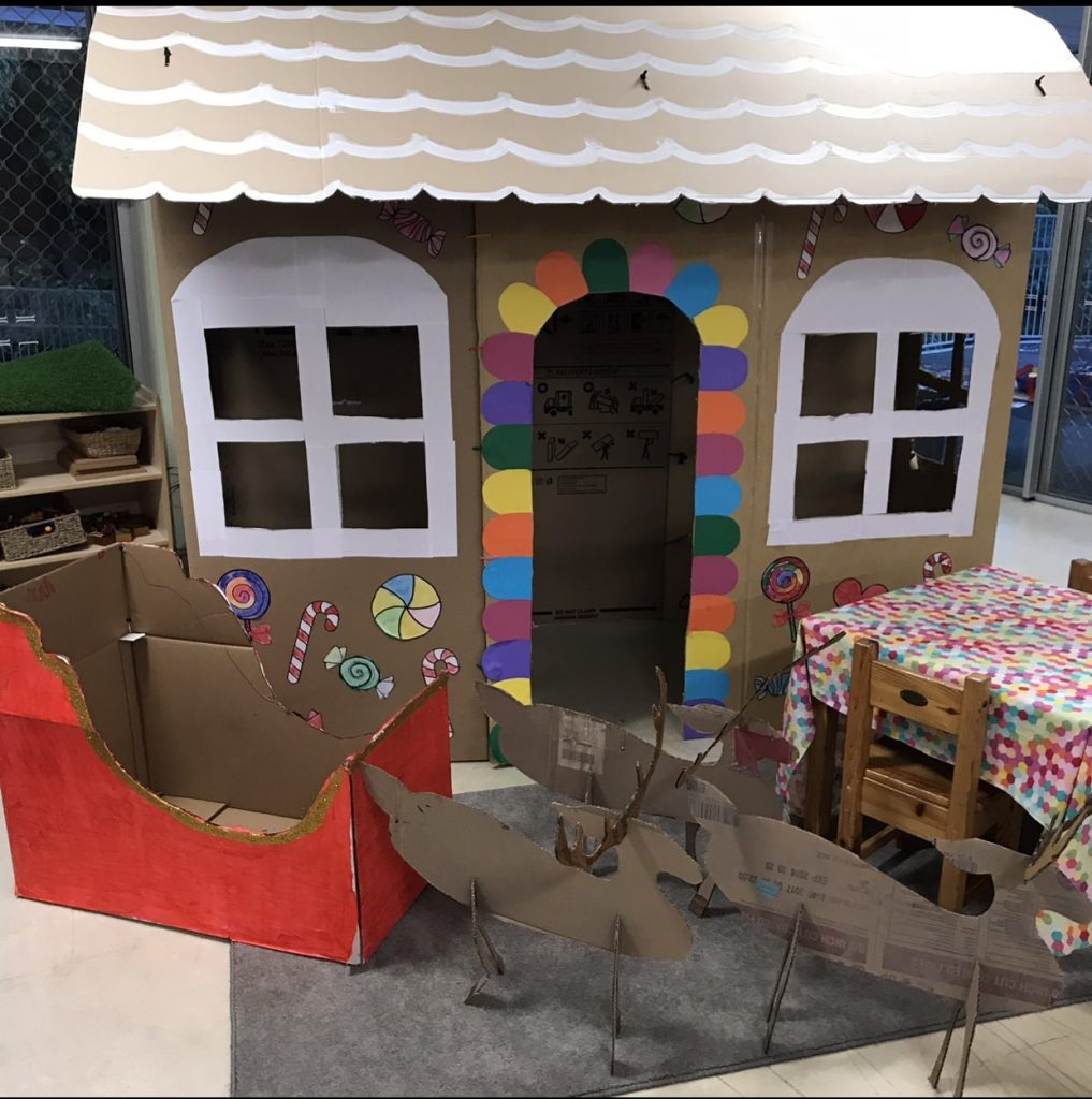 Christmas pretend play featuring cardboard craft house
