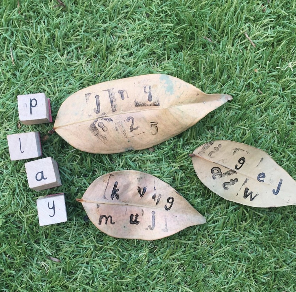 Alphabet cubed stamps are used to print letters on dried leaves