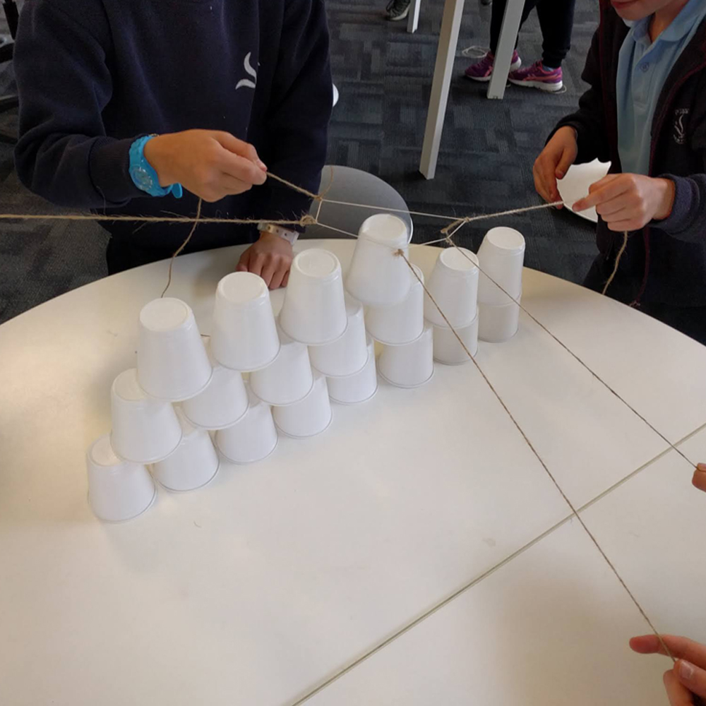 Makerspace cup towers challenge close up with kids hands