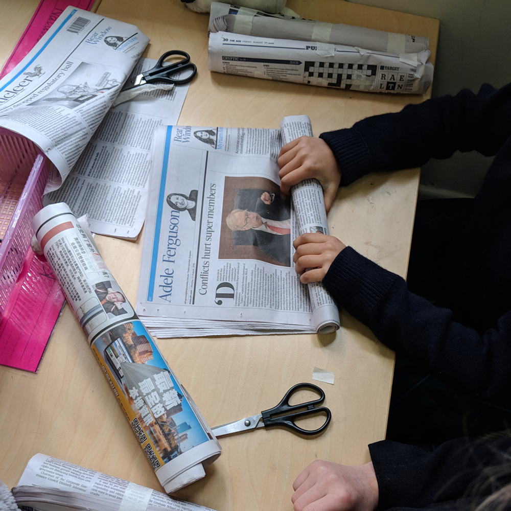 Makerspace newspaper challenge showing kid rolling newspaper on desk
