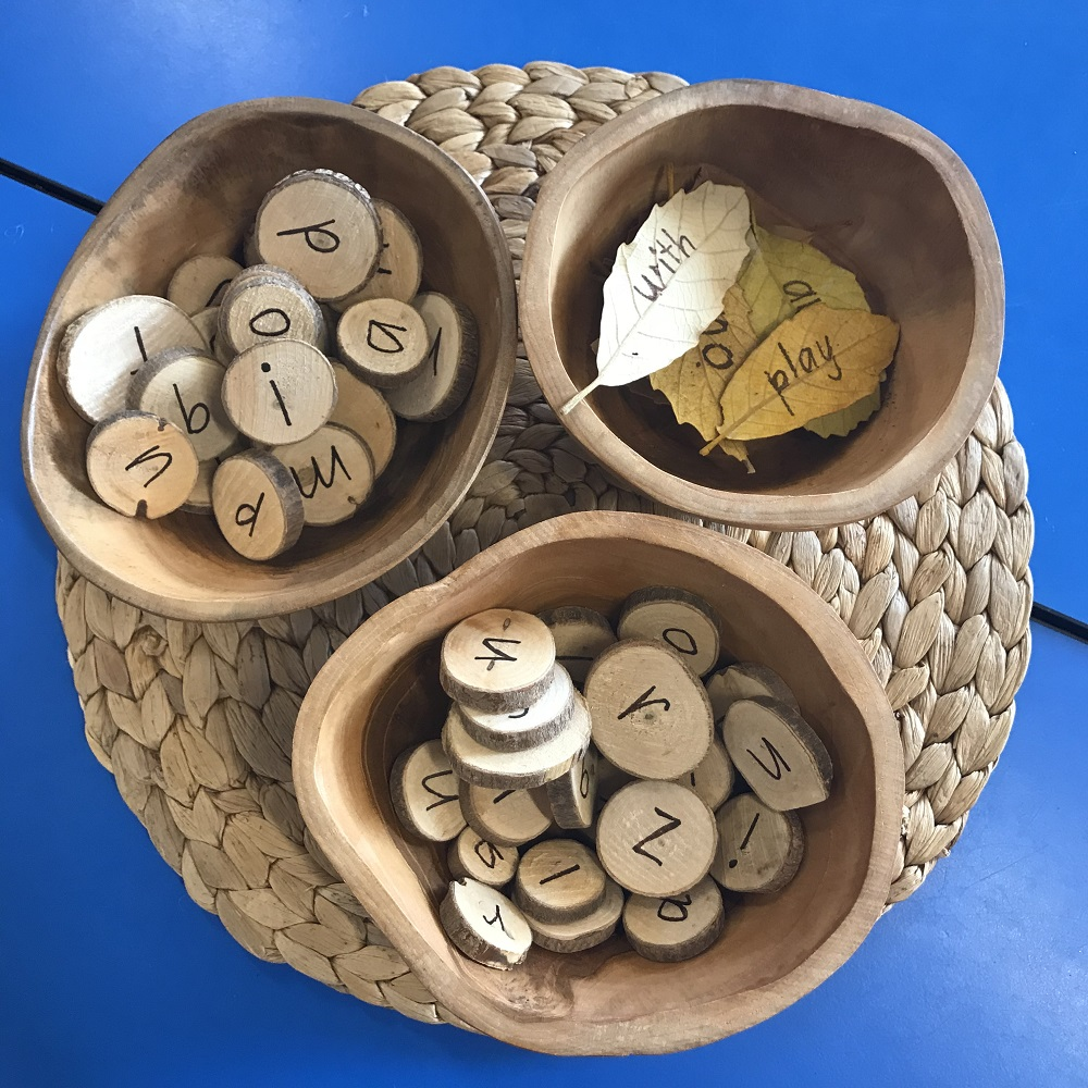 Letters written on wooden slices placed in wooden sorting bowls