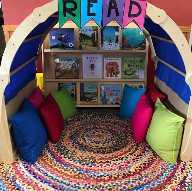 Reading corner featuring cushions books and reading arch