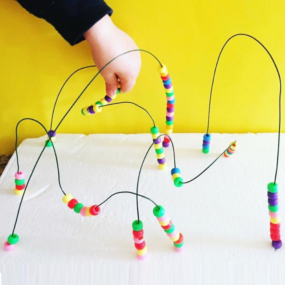 Child moving beads around a wired maze