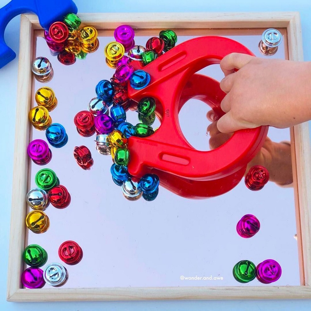 Child picking up bells with a large magnet