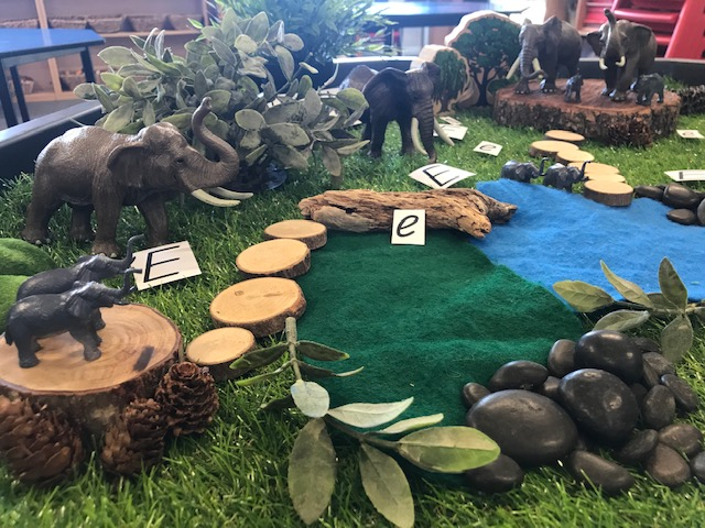 Natural resources used to create a small world replicating a jungle featuring rocks, twigs, leaves, branch cut circles for stepping stones, sticks and pine cones