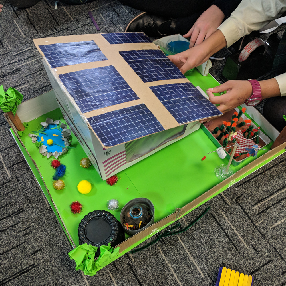 Child creating Sam Labs sustainability house with solar panels and garden made out of card