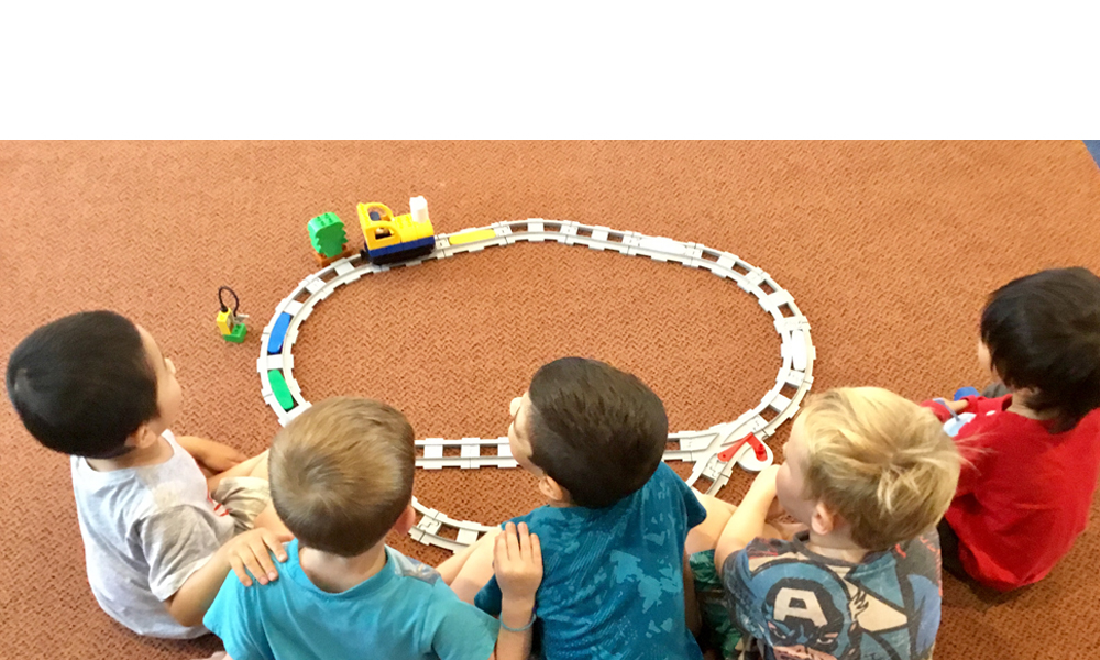 Five children sat on the floor playing with a Coding Express train
