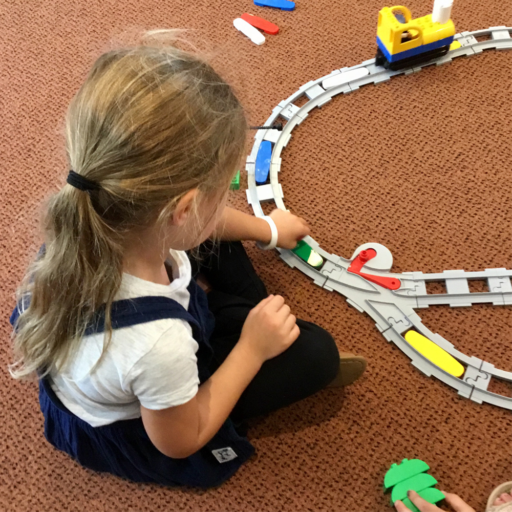 Young girl building a Coding Express train track