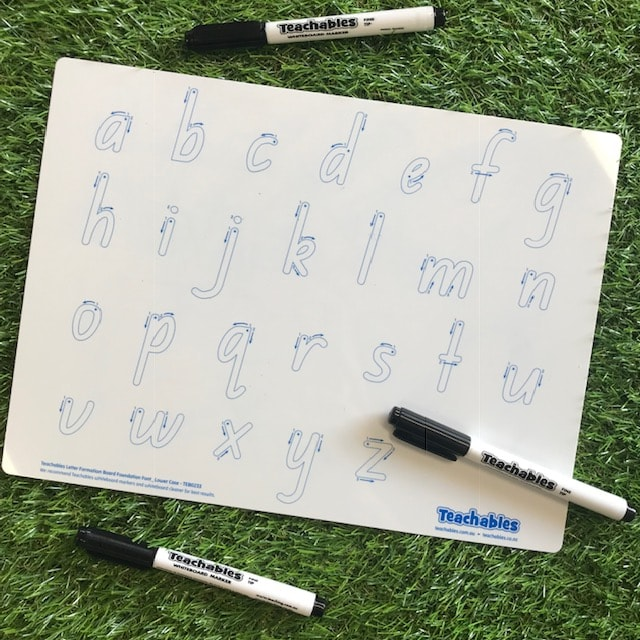 alphabet whiteboard and pen on grass background