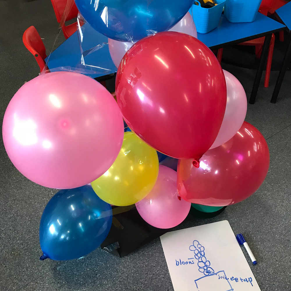 Balloons stacked in a tower with a drawing on paper of intended outcome