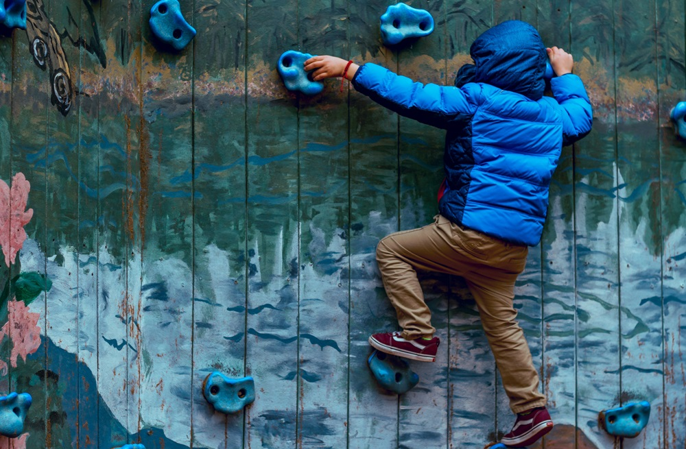 Boy in blue jacket reaching for rock climbing hold