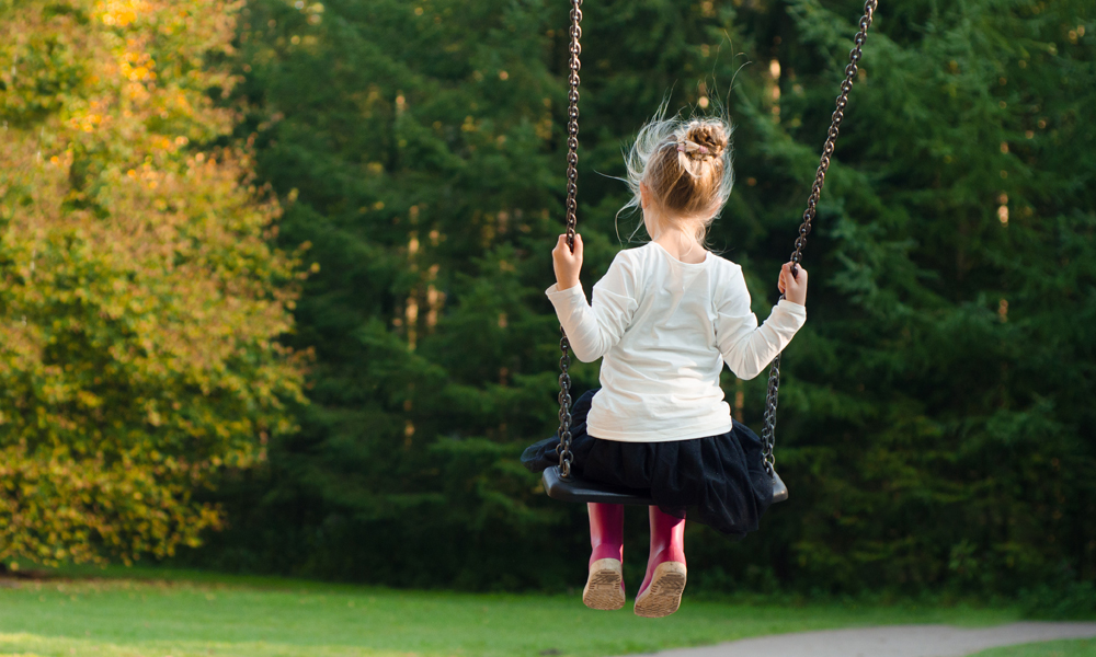 Girl playing on swing outside facing grass and trees