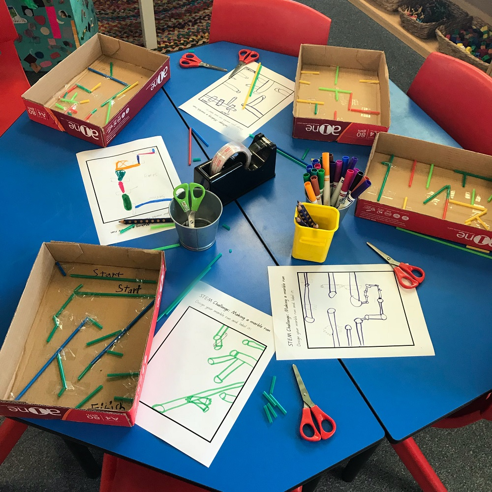 Four marble maze activities in progress on a classroom table