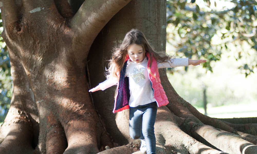 Young girl exploring whilst walking over tree roots