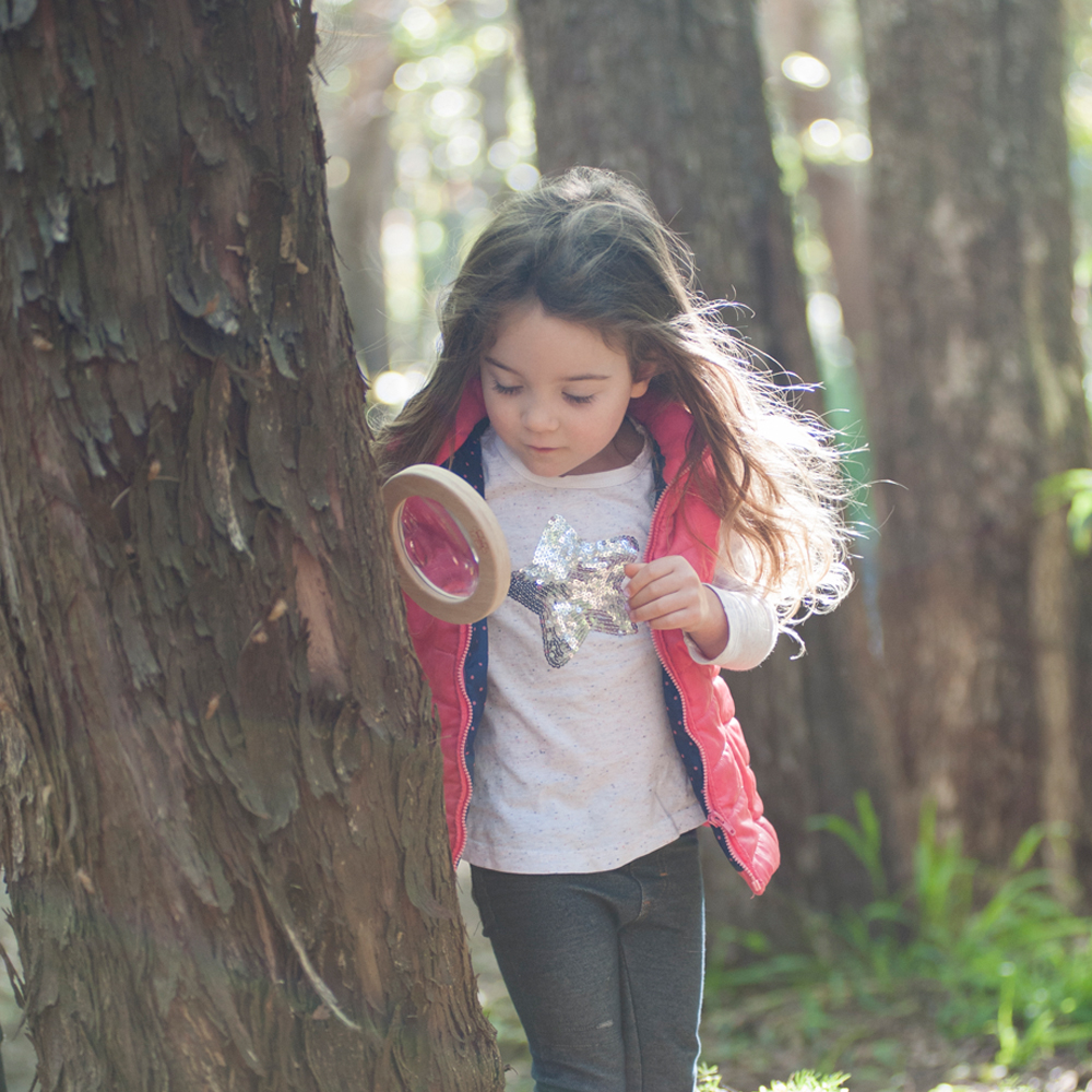 Young girl exploring the outdoors with magnifier glass