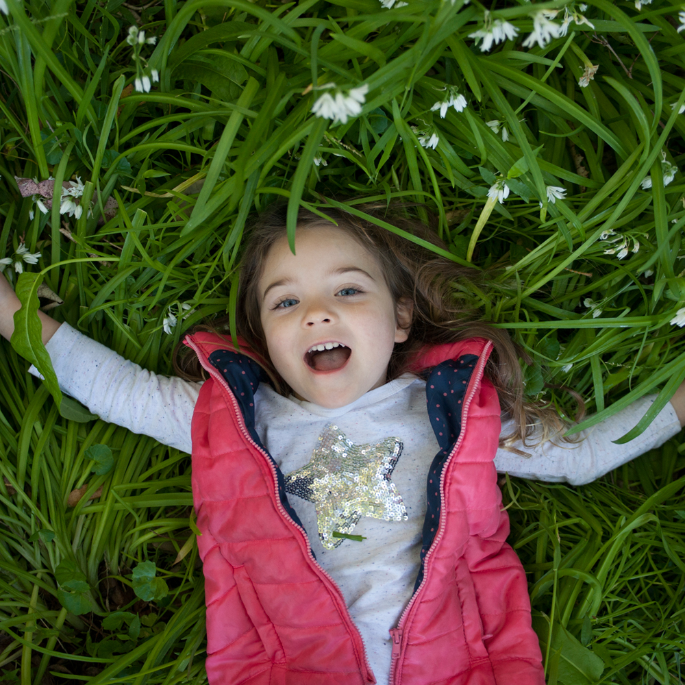 Young girl laying down on Grass