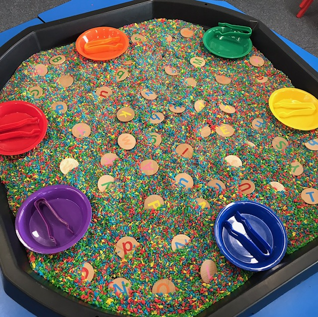 Active world tray  filled with coloured rice and alphabet discs