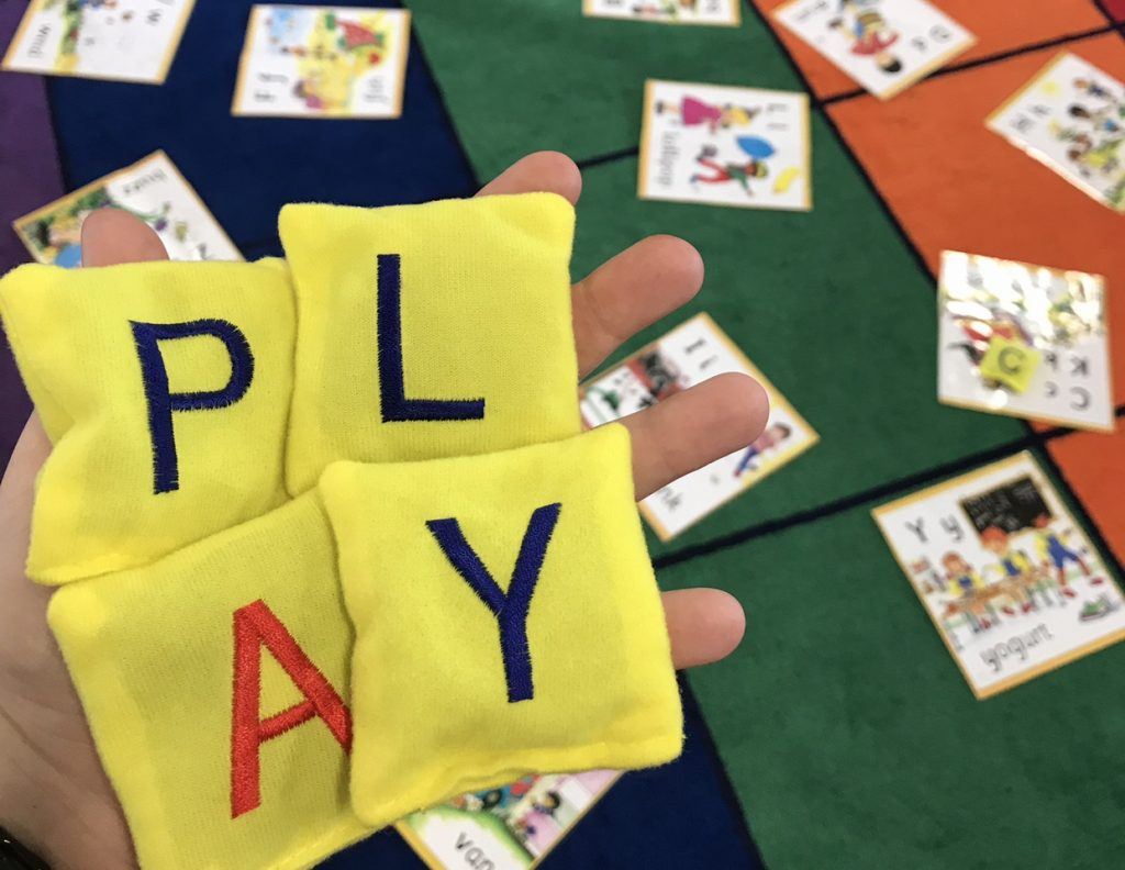 Alphabet bean bags activity close up of word PLAY spelt out in kids hand