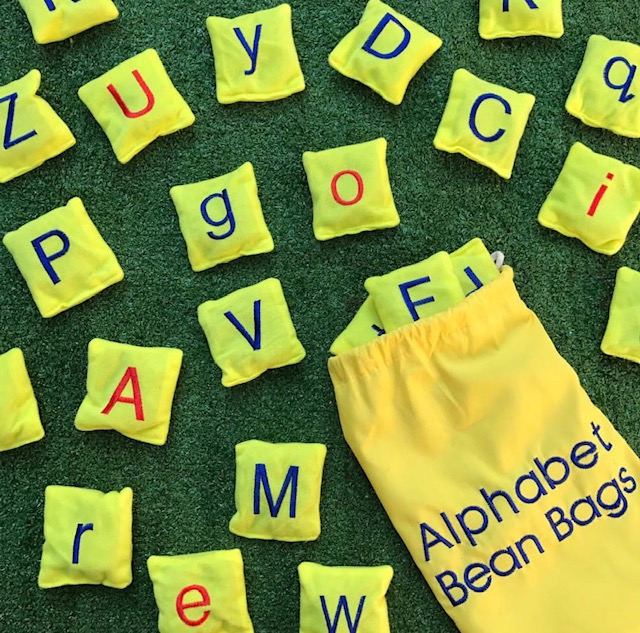 Alphabet bean bags on grass background