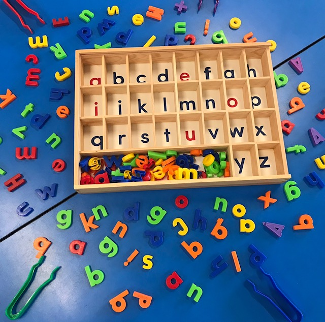Alphabet sorting tray on desk with magnetic letters