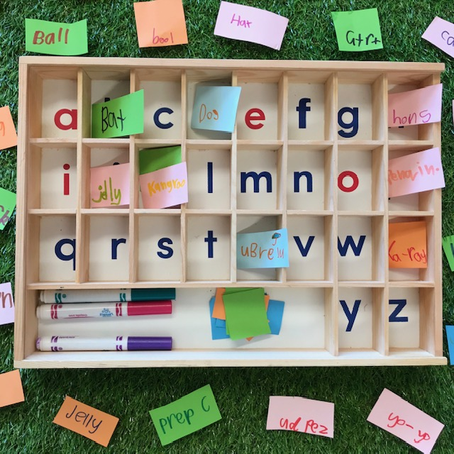 Alphabet sorting tray activity with post it notes and felt pens on a grass background