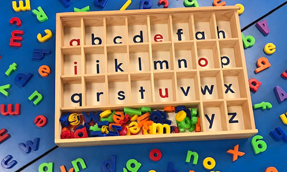 Close up of alphabet sorting tray and magnetic letters on classroom desk