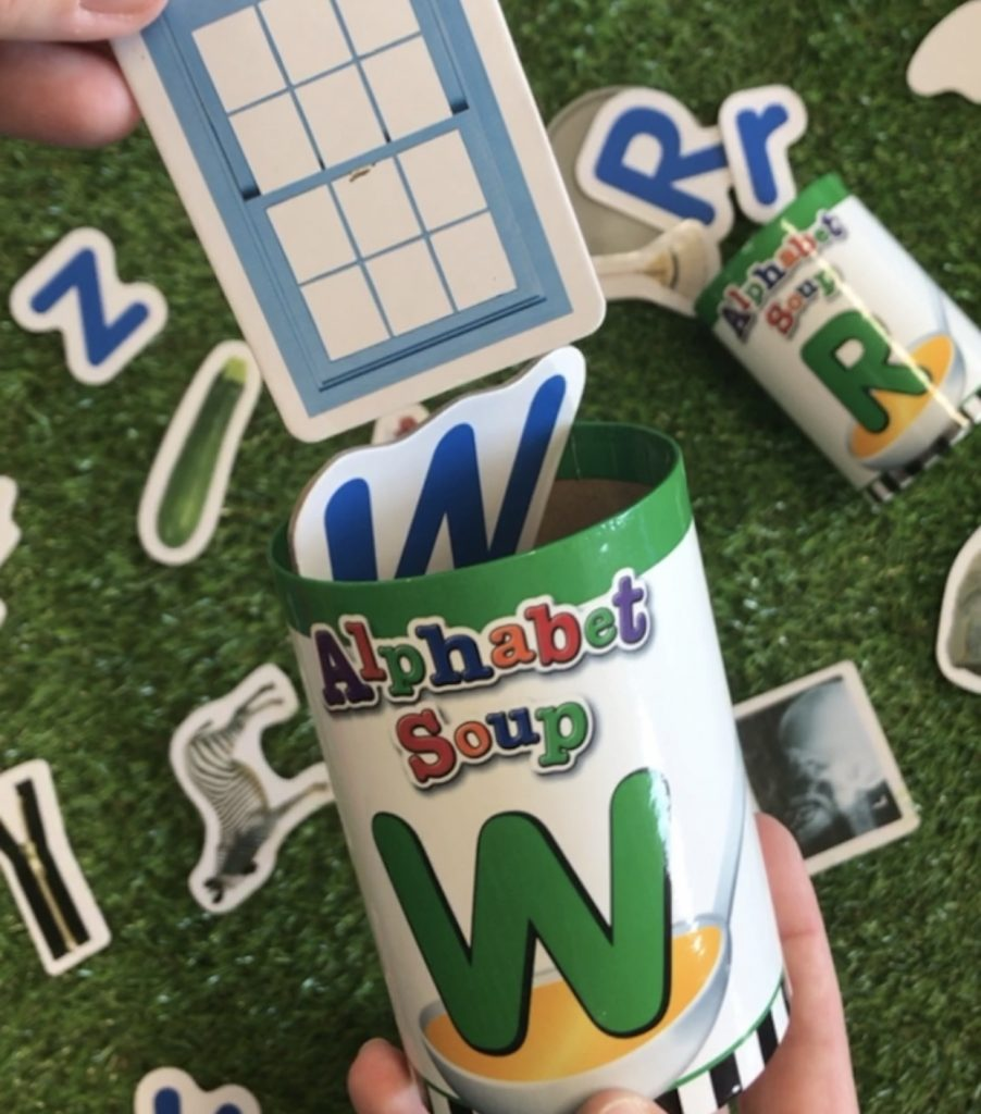Alphabet soup sorter cans close up on grass background