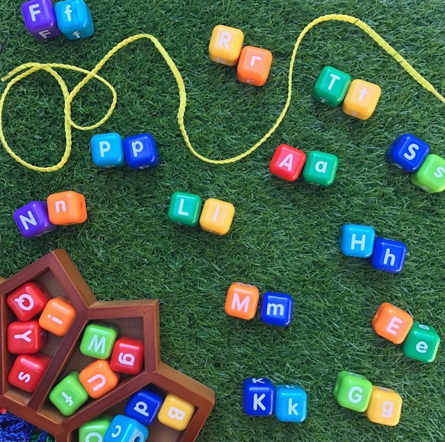 Chunky alphabet beads letters on grass background