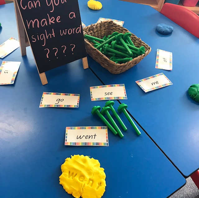 Lowercase alphabet dough stampers activity featuring blackboard on desk prompting students to make a sight word with the dough and stampers