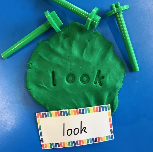 Lowercase alphabet dough stampers spelling out the word look into green dough