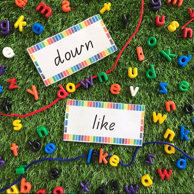 Lowercase letter beads threading activity on grass background