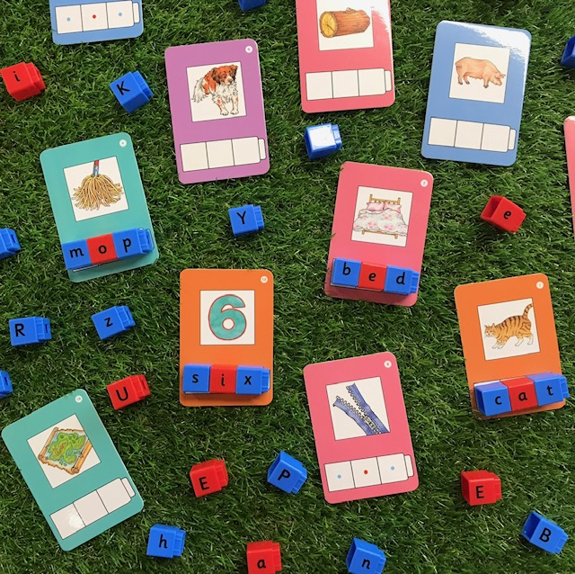 Phonic cvc matching activity featuring alphabet blocks and  CVC prompt cards on a grass background
