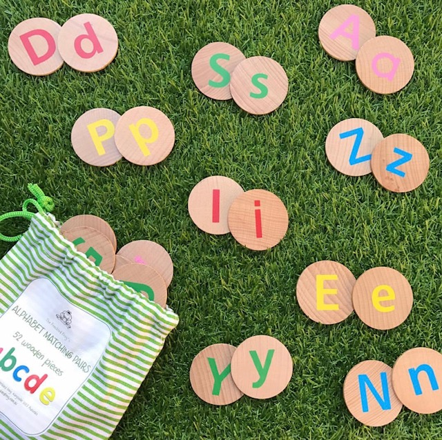Wooden upper and lowercase alphabet discs on grass background
