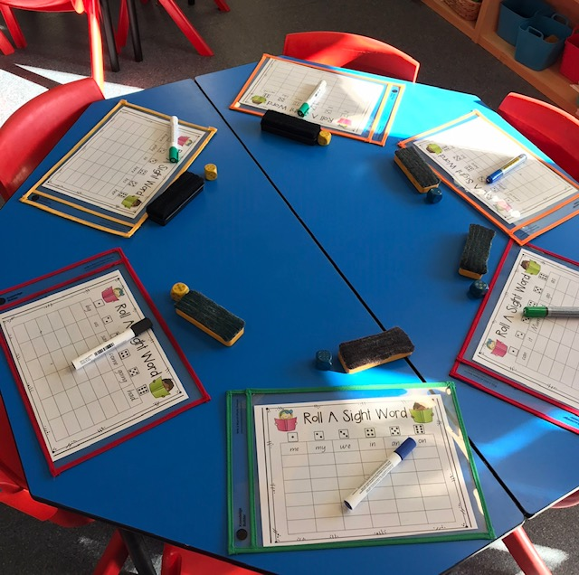 Write and wipe sleeves activity featuring whiteboard pens and markers on classroom desk